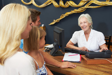 Hotel Receptionist Helping Family To Check In