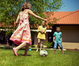 Happy family playing football in the garden