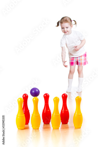 Kid girl throwing ball to knock down toy bowling pins. Focus on