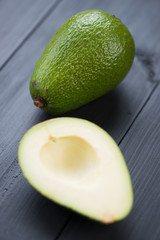 Vertical shot of a whole ripe avocado and its half