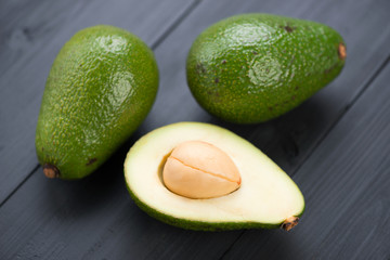 Ripe avocados on black wooden boards: whole and cut