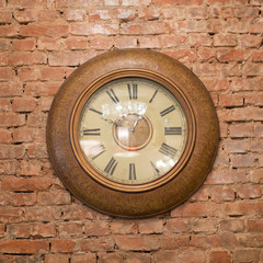 An old style antique clock on a brick wall