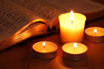 Close-up of candles and open Bible..