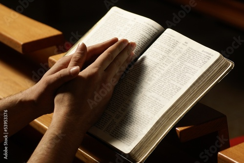 Hands on Holy Bible in prayer at church