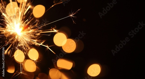 Close-up of sparkler on Christmas lights background