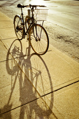 Bicycle locked to the rack and its shadow