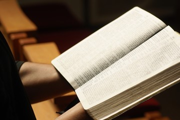 Hands holding open Bible at church