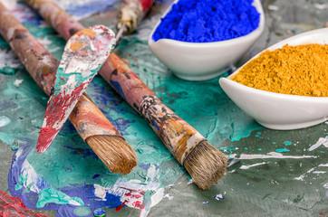 Pinsel, Spachtel und Farbpigmente auf einer Holzpalette