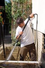 Mann reinigt Treppenstufe mit Hochdruckreiniger