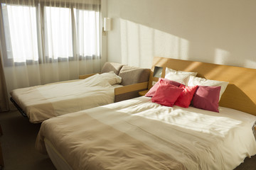 budget bedroom with two beds with red pillows and window