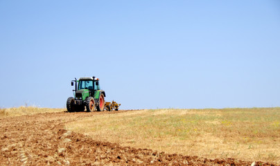 Tractor plowing the dry field