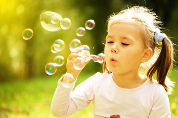 Little girl is blowing a soap bubbles