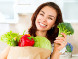 Happy Young Woman with vegetables in shopping bag. Diet Concept