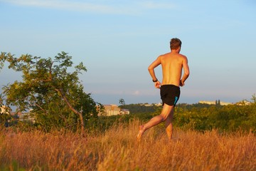 Young man is running on summer meadow