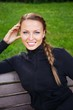 Young beautiful sporty woman sitting on a bench in a park