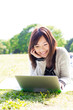 young asian woman using laptop in the park
