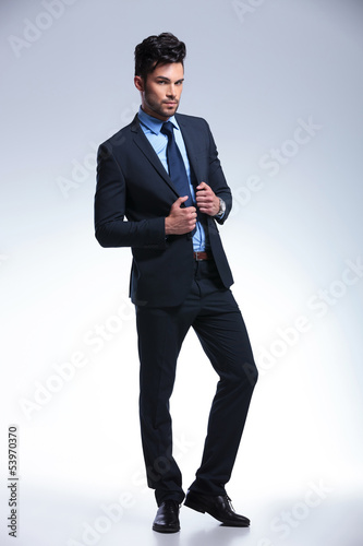 business man stands with hands on jacket