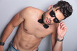 topless young man holds his sunglasses