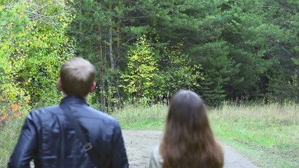 Young man and woman walking  in the park, hand in hand.