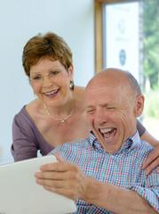 Seniorenpaar Best Ager freut sich mit Tablet