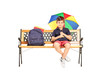 Schoolboy sitting on a bench and holding colorful umbrella
