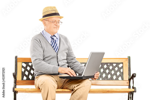 Senior man sitting on a wooden bench and working on a laptop