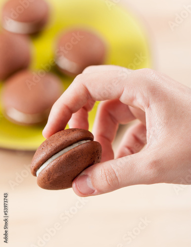 Hand holding a chocolate and vanilla whoopie