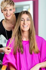 Frau bei Friseurin erhält Haarschnitt