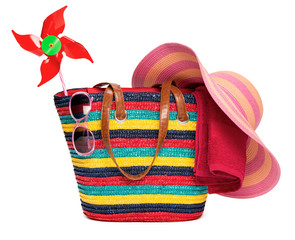 Colorful striped beach bag with a straw hat towel sunglasses and