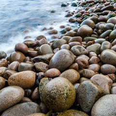 Wet pebbles on beach with blurred water, Maine, USA