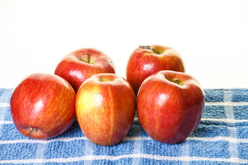 Five Red Apples on Blue Towel