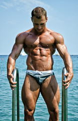 Attractive young bodybuilder getting out of sea or ocean