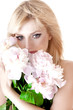 Sensual portrait of a blond woman with flowers on a white