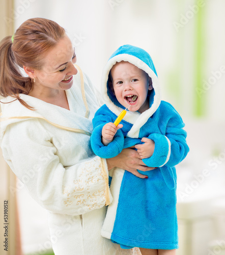 mother and child brushing teeth together in bathroom. Dental hyg
