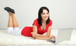 Beautiful young woman lies with notebook in room