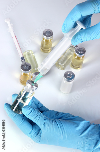 Medical bottles and syringes in hand on gray background