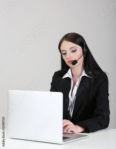 Call center operator at work, on gray background