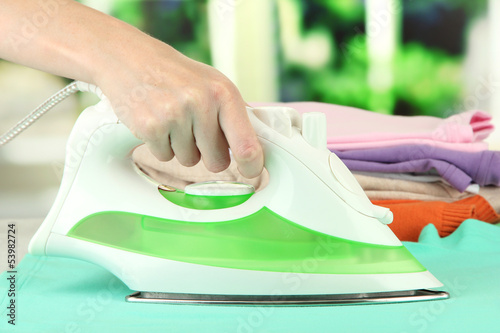 Woman's hand ironing clothes, on bright background
