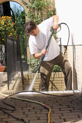 Mann reinigt mit Hochdruckreiniger Kelleraufgang