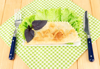 Tasty cheburek with fresh herbs on plate,on wooden background