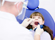 dentist using dental filling gun on kid