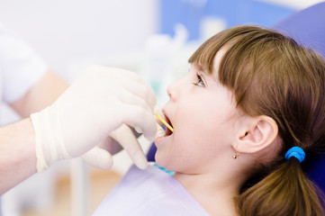dental examining being given to little girl by dentist