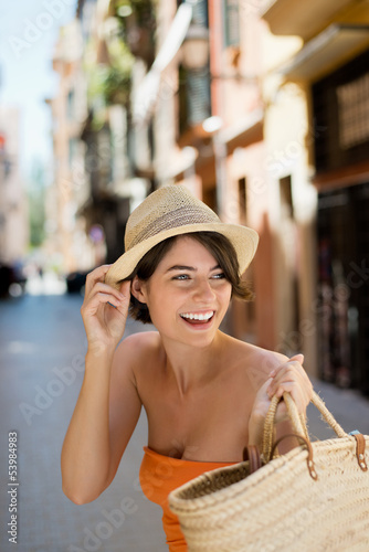 lachende junge frau mit korb in der stadt