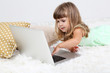 Little cute girl lies on carpet with laptop, on gray background