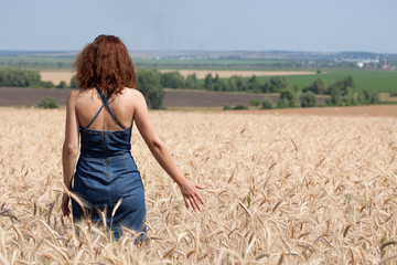 Woman in a wheat field on a summer day