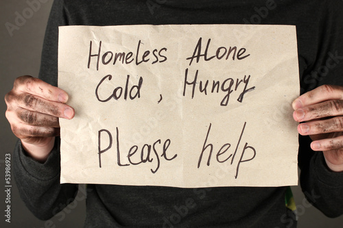 homeless man asks for help, on black background close-up