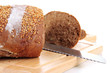 Bread with sesame seeds and knife on wooden board close up
