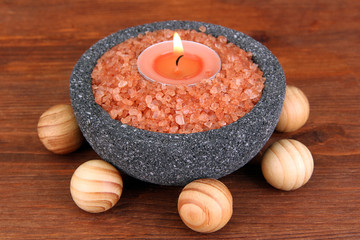 Candle in stone bowl with marine salt, on wooden background