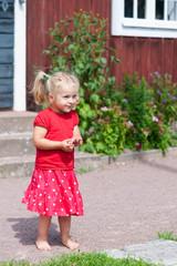 Kleines blondes Mädchen in rotem Sommerkleid
