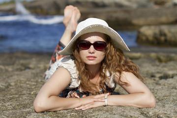 sahilde güneşlenen gözlüklü ve şapkalı bayan